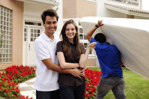 new homeowners standing happily in front of home while mover brings in furniture