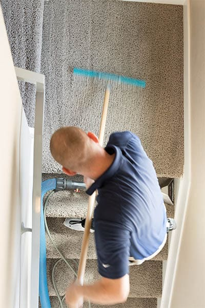 MSS Cleaning employee using a carpet rake to groom carpet