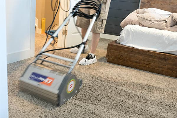 Uniformed MSS Cleaning employee using counter rotating brush machine to deep clean carpet