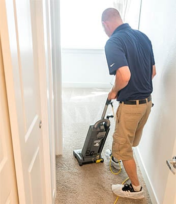 Uniformed MSS Cleaning employee vacuuming carpet in Cherry Creek prior to carpet cleaning