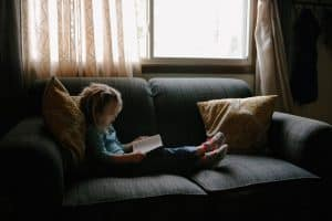 Little girl sitting on grey sofa reading a book