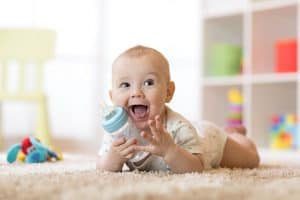 baby with bottle of milk lying on a carpet