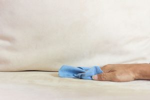 using a cloth to clean microfiber sofa