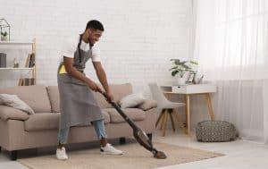 Man vacuuming rug in home